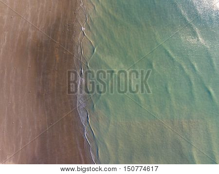 Aerial View Of Green Sea Lapping On Sandy Beach
