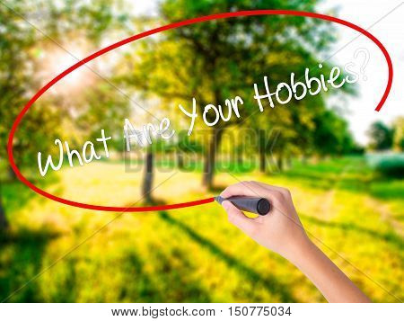 Woman Hand Writing What Are Your Hobbies? With A Marker Over Transparent Board
