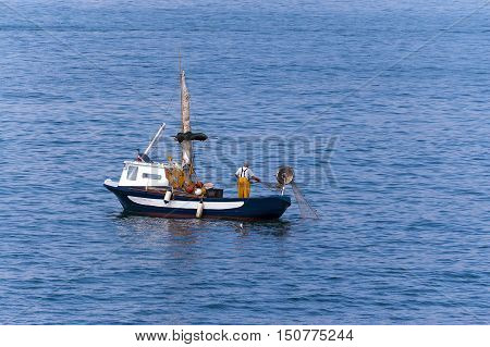 Fisherman on a small blue and white boat with fishing net between the waves of the sea. Liguria Italy