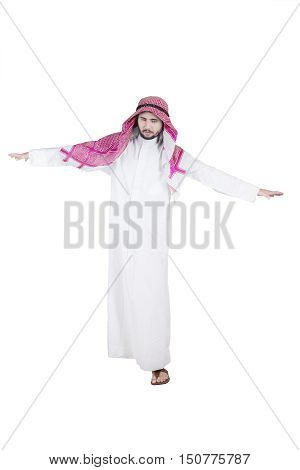 Full length of Arabian businessman walking on invisible rope in the studio