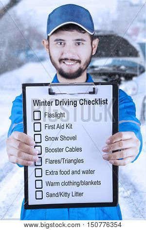 Young Asian mechanic holding a clipboard and showing a winter driving tips shot outdoors