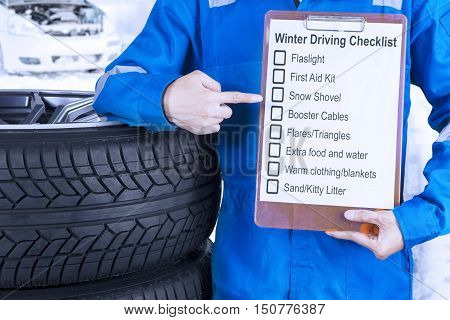 Close up of a car mechanic leaning on a pile of tires and showing a winter driving tips on the clipboard
