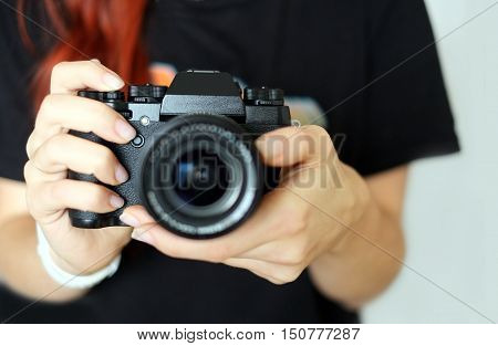 The professional girl photographer with red hair in a black shirt holds modern black color camera with lens pointing forward. Horizontal indoor studio fashion photo close-up on a gray background