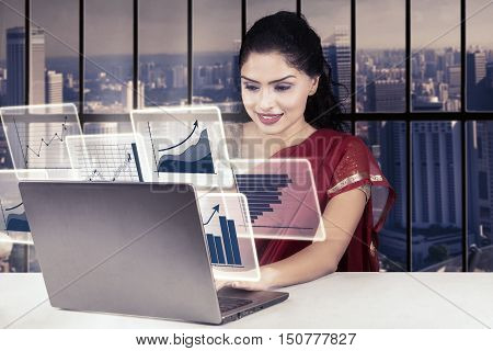 Indian businesswoman working in the office while wearing saree clothes and using laptop with virtual financial graph