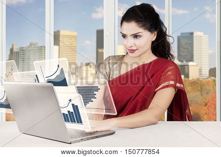 Indian young businesswoman working with virtual financial statistic on the laptop shot in the office