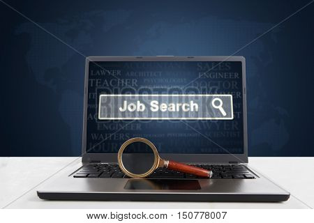 Picture of a laptop computer with a job search text on the screen and a magnifier on the keyboard
