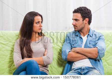 Young couple is sitting on sofa at home. They are angry and not talking to each other.