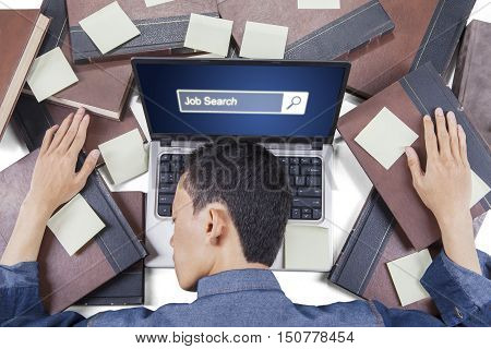 Concept of Job Search. Exhausted man sleeping with jobs search bar on the laptop screen and book