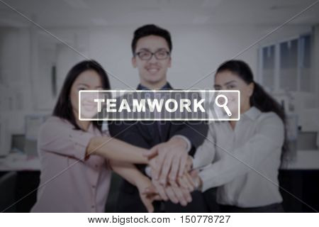 Image of a search button with teamwork text and a group of business team joining hands together