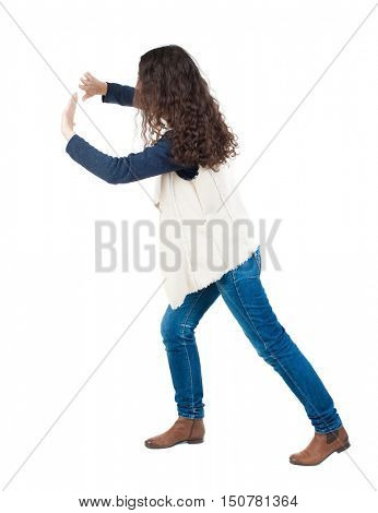back view of woman pushes wall. Isolated over white background. Rear view people collection. backside view of person. curly girl put her hands on the obstacle. A girl in a white tank top is pushing