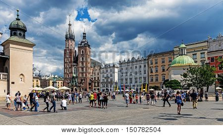 KRAKOW POLAND - AUGUST 15 2016: Old Market Square crowded with tourists at the St. Mary's Basilica brick Gothic church built in the early 13th century is the main landmark of the city.