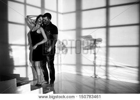 Romantic sensual couple posing in modern interior at sunset light. Fashion style portrait of young sexy girl and handsome man hugging. Fine art photo with cool shadows
