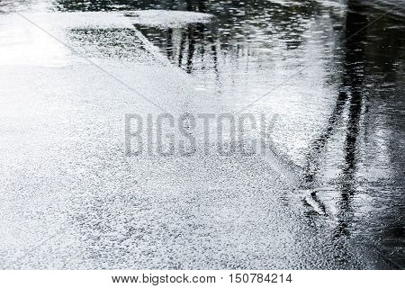 Water Puddles With Raindrops Falling On Them On Wet Asphalt