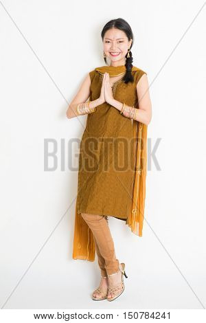 Portrait of mixed race Indian Chinese girl in traditional punjabi dress greeting, full length standing on plain white background.