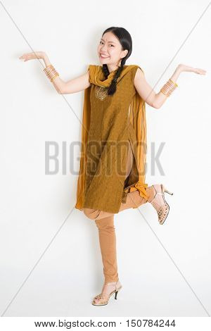 Portrait of excited mixed race Indian Chinese girl in traditional punjabi dress palms showing something, full length standing on plain white background.