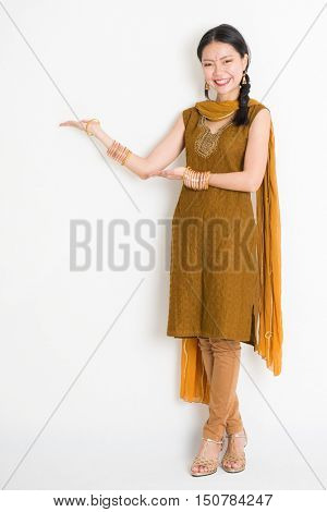 Portrait of young mixed race Indian Chinese woman in traditional punjabi dress hands showing somethings, full length standing on plain white background.