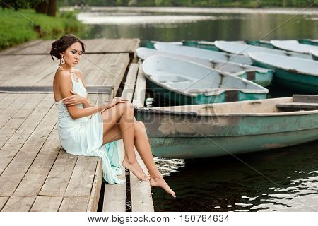 Young beautiful girl in blue dress sitting at wooden pier near boats