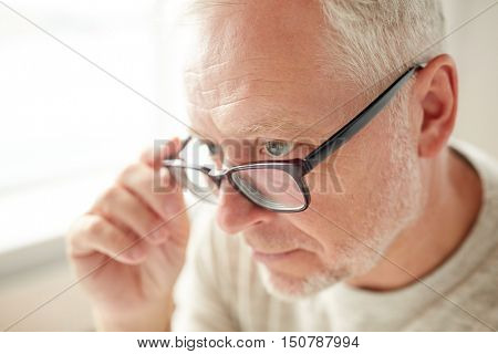 old age, eyesight, vision, optic and people concept - close up of senior man in glasses looking