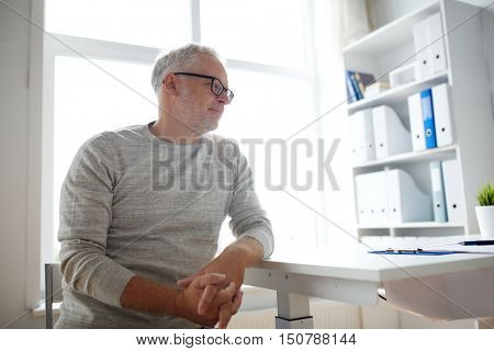 old age, problem, healthcare and people concept - sad senior man sitting at table at medical office