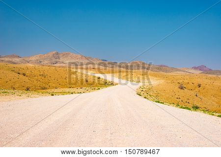 Gravel Winding Road Crossing The Colorful Namib Desert, In The Majestic Namib Naukluft National Park