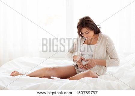 pregnancy, love, people and expectation concept - happy pregnant woman sitting on sofa and making heart gesture at home bedroom