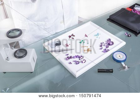 The Gemologist expertise in her laboratory fix the value of precious stones and pearls; using optical fibers Hydrostatic Balance Polariscope Refractometer Dichroscope.