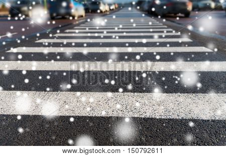 safety, traffic laws, highway code and road sign concept - close up of pedestrian crosswalk on city car parking over snow
