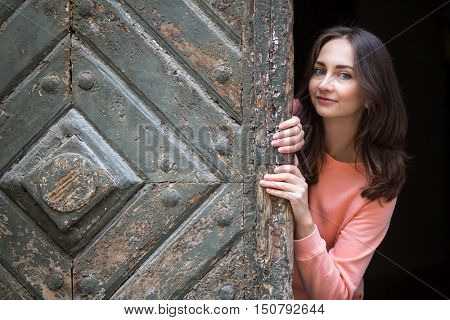 Young cute girl peeks out from behind vintage doors.