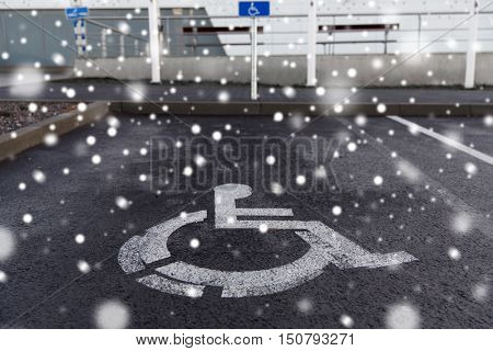 traffic laws and highway code concept - car parking road sign for disabled outdoors over snow