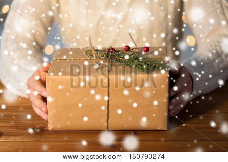 christmas, holidays, presents, new year and people concept - close up of woman with gift box or parcel wrapped into brown mail paper and decorated with fir brunch