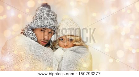 people, christmas, holidays and new year concept - freezing couple in winter clothes wrapped in plaid over holidays lights background