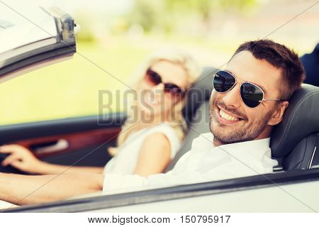 road trip, dating, leisure, couple and people concept - happy man and woman driving in cabriolet car outdoors