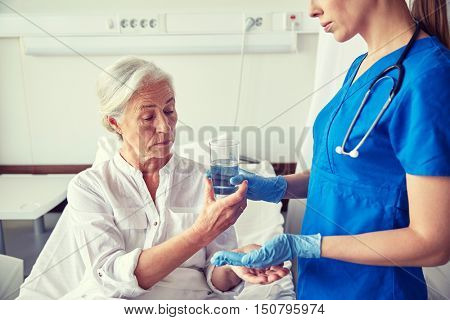 medicine, age, health care and people concept - nurse giving medication and glass of water to senior woman at hospital ward