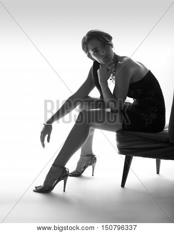 Beautiful sitting woman instudio in black dress, with high heel shoes, white background