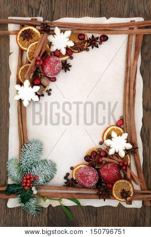 Christmas abstract background border with cinnamon sticks, gingerbread cookies, spices, dried orange, apple and cranberry fruit with holly, fir and mistletoe on parchment paper over oak wood.