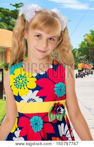 Sweet, adorable little girl with long blonde ponytails on her head tied with white bows. Close-up.On the background of the road, palm trees and blue sky with clouds.