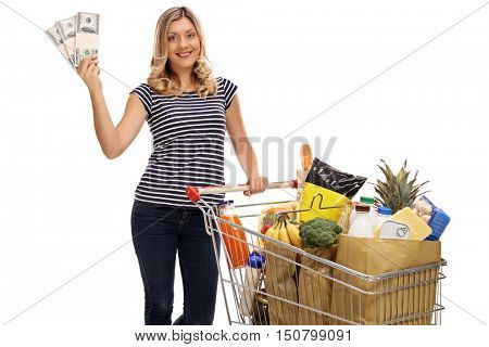 Happy woman posing with a shopping cart full of groceries and bundles of money isolated on white background