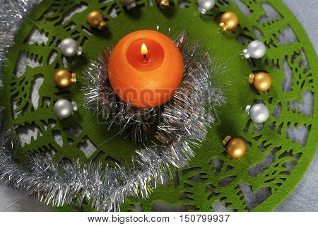 Merry Christmas greeting card made of green christmas mat silver tinsel with silver and golden christmas balls and orange candle against silver background horizontal top view