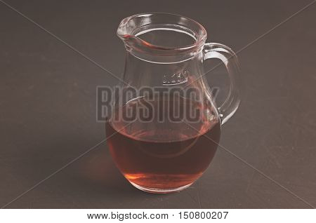 glass jug with infusion of oak bark at blackboard