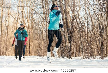 Group of millenial young adult friends training for cross-country running in the wintertime in a snow-filled park