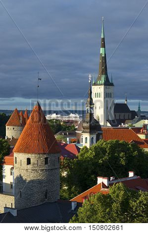 The old Oleviste Church and the defensive tower under a cloudy sky. Historical landmark of the Old Tallinn, Estonia