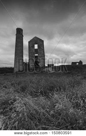 Some derelict buildings including a chimney at a disused mine Magpie Mine in the Peak District