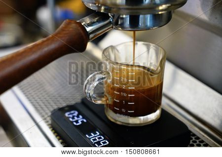 preparing espresso on professional coffee machine with weight measure
