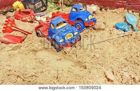 Forgotten of childhood cars in sandbox at summer day