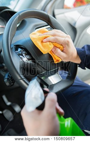 Close Of Man Cleaning Interior Of Car