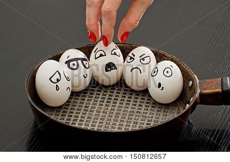 Eggs with painted emotions in a frying pan a female hand takes one of them