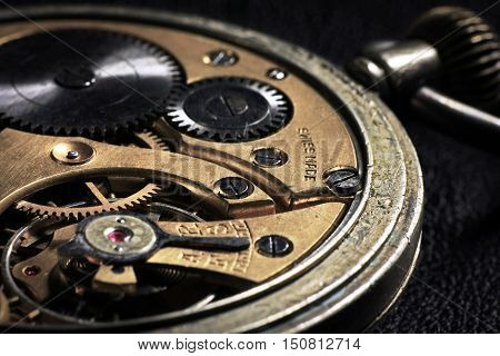 Pocket watch inside with wheels and springs close up on dark background