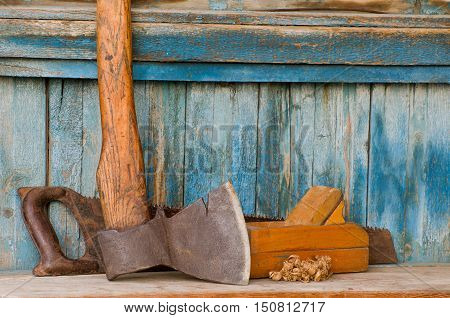 Axe planer and saw on an old wooden background chips