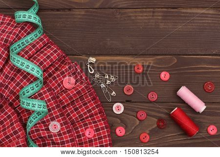 Red fabric , thread, measuring tape and buttons on the wooden table. The view from the top. Sewing accessories.