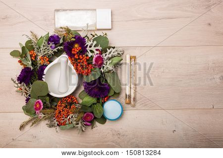 Seasonal Skincare Products With Flowers On A Wooden Background